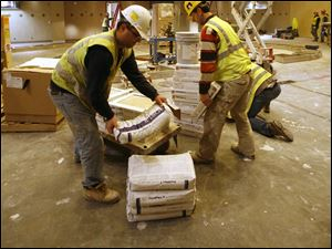 Andy Orgocka, left, and Ari Duro of PMP Marble and Granite of Troy, Michigan, unload materials for the floor in the dining area of the Hollywood Casino.