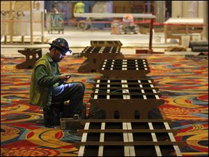 A worker works on wiring on the base for a slot machine.