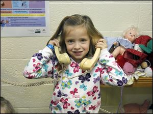 Kindergartner Madi Hammer uses her imagination and a couple of telephones for an activity during recess at Solomon Lutheran School in Woodville. The school opened its doors Jan. 20, 1862.