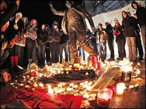 Candles and memorabilia are placed by well wishers at the foot of a statue of Joe Paterno outside Beaver Stadium on the Penn State University campus Saturday.