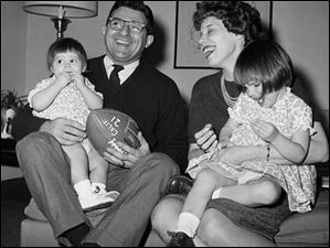 In 1966, Joe Paterno, new head football coach at Penn State, left, poses with his 2-year-old daughter Diana Lynne Paterno, right on mother's lap, his wife Suzanne Paterno and their 1-year-old daughter Mary Kathryn Paterno, on father's lap, in his home in State College, Pa.