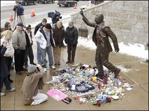 People gather around a statue of Joe Paterno outside Beaver Stadium on the Penn State University campus after learning of his death Sunday in State College, Pa.