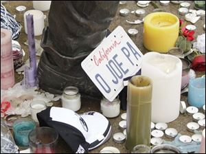 Items left at the foot of a statue of Joe Paterno lie outside Beaver Stadium on the Penn State University campus after news of his death Sunday in State College, Pa.