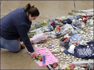 Laura Scott of State College, Pa., places a rose at the foot of a statue of Joe Paterno outside Beaver Stadium on the Penn State University campus after learning of his death Sunday in State College,Pa.