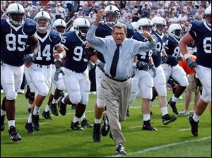 Penn State coach Joe Paterno leads his team onto the field before an NCAA college football game against Akron Sept. 4, 2004, in State College, Pa.