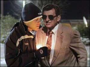David Marselles, a senior at Penn State from Allentown, Pa., stands with a cardboard cutout of Joe Paterno near a statue of Paterno outside Beaver Stadium on the Penn State University campus Saturday in State College, Pa., after Paterno's doctors said the former coach's condition has become 'serious' after he experienced complications from lung cancer in recent days.