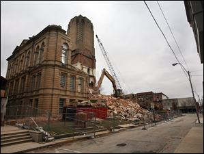 The outer walls of the courthouse are turned into rubble by the wrecking crew.