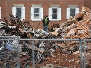 A construction worker stands atop the rubble of the former 1884 courthouse.