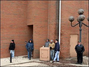 Spectators watch the demolition of Seneca County's courthouse Tuesday, Jan. 24.