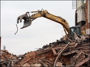 A machine and its operator sift through the wreckage of the Seneca County Courthouse.