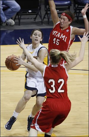 Toledo's Courtney Ingersoll drives between Miami's Kirsten Olowinski (45) and Hannah Robertson (32). Ingersoll scored eight points as the Rockets defeated the RedHawks to stay atop the West Division.