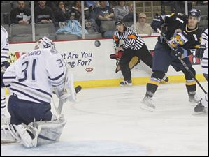 Walleye player David Gilbert takes a shot against Express goalie Peter Mannino in the first period.
