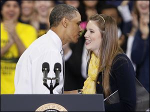Obama speaks to University of Michigan student Christina Beckman after she introduced him to the crowd. He talked about education and requiring universities to keep tuition costs down.