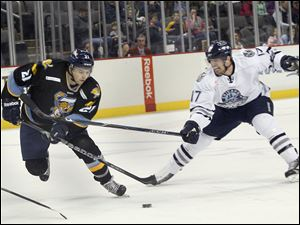 Walleye player #21, Bryan Rufenach, contends with the stick of Express player #17, Aaron Marvin.