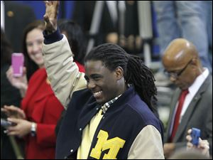 Denard Robinson, quarterback for the University of Michigan football team, acknowledges the applasue of the crowd after he was recognized by Obama during his appearance at the Al Glick Field House.