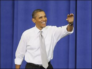 President Barack Obama waves to the crowd as he enters the Field House.