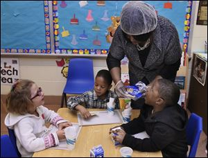 Teacher Joyce Wilson hands out pastry snacks for children in her Head Start class at Mayfair School in Toledo. More than 2,000 children in Lucas County are enrolled in Head Start, a program for low-income 3-to-5 year-olds.