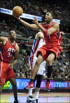 Atlanta Hawks' Tracy McGrady (1) goes past Detroit Pistons' Austin Daye for a basket as Hawks' Jason Collins (34) looks on in the first half of an NBA basketball game on Friday, Jan. 27, 2012, in Auburn Hills, Mich. (AP Photo/Duane Burleson)