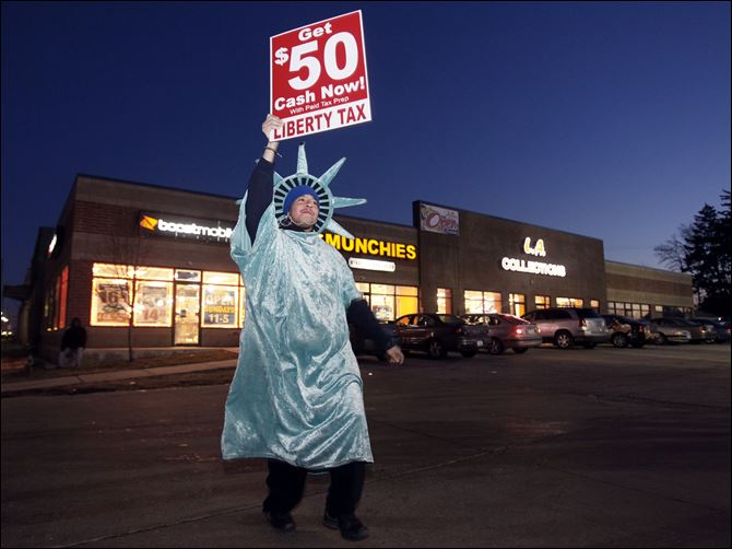 Isaac Underwood, a Statue of Liberty mascot for Liberty Tax Services on Monroe Street near Auburn Avenue, promotes the company's services the day after the office was robbed. Although he has been a Liberty employee for three years, Thursday, the day of the holdup, was his first at the site.