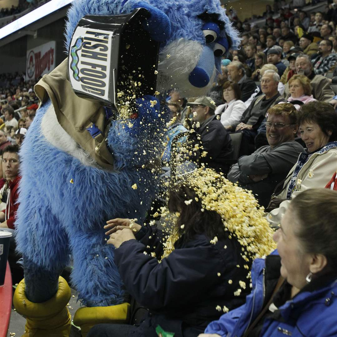 Toledo-mascot-Cat-Trick-dumps-a-bucket-of-popcorn-on-fan-Sylvia-Spencer