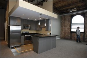 The inside of the Standart Lofts shows the stainless steel appliances and granite countertops, plus the exposed red brick, wood support beams, and high ceilings of bare wooden slats.