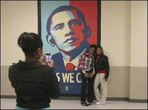 From left, Janecia Taylor takes a picture of Charleigh Lemley and Janee Joyce in front of the new Presicent Obama mural as they tour the newly renovated Scott High School.