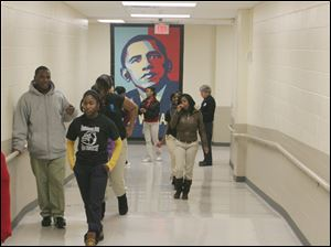 Scott High School students walk past a mural of President Obama.