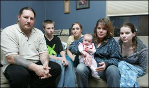 William Erb III sits with members of his East Toledo household Billy Erb, 17, Ashley Erb, 16, Stacy Erb holding granddaughter Sierra Kramer, and Christine Brooks, 19.
