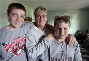 Tricia Askins and her sons Jared Rettig, 12, left, and Jacob Rettig, 10, moved into her parents' home at the fi rst of the year after she was laid off three times from the same factory job.