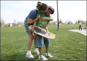 Shaun Purley plants a kiss on her son, Jordan, before he heads off to the skateboard area at Highland Park.