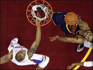 Cleveland Cavaliers' Ramon Sessions, right, shoots over Los Angeles Clippers' Caron Butler in the second quarter Wednesday night.
