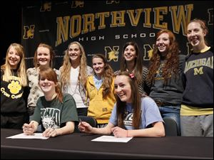 Northview High School cross country teammates Maureen Dean, seated left, and Alison Work, seated right, pose with teammates after sign their national letters of intent to attend their respective colleges, during a ceremony at Northview.  Dean will attend Ohio University and Work will attend Grand Valley State.  Teammates standing from back left are Abby Masters, Katelyn Work, Robin Foster, Laura Judge, Mallory Small, Morgan Vince, Esther Haviland.