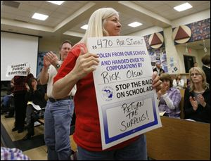 Jane Crafts, president of the Bedford Transportation Association, makes her feelings known at last week's Bedford board of education meeting as other attendees applaud.