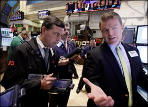 Specialist Michael O'Mara, right, works on the floor of the New York Stock Exchange.