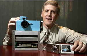 Steven J. Sasson, then-project manager for Eastman Kodak Co., shows the prototype digital camera he built in 1975, left, and Kodak's EasyShare One at the firm's headquarters in 2005. Kodak said Thursday it no longer will make digital cameras or pocket video cameras.