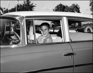 10-year-old Mitt gets behind the wheel of a Nash, an automobile manufactured by American Motors Corp., of which his father, George, was president. Young Romney had a great interest in cars.