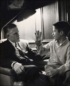 A young Mitt Romney talks with his father, George, at their Detroit-area home in 1957.
