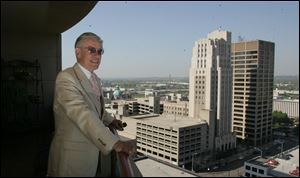 Ed Rhodes, a retired school principal, enjoys the view from his 15th-fl oor condo near Dayton's performing arts center.