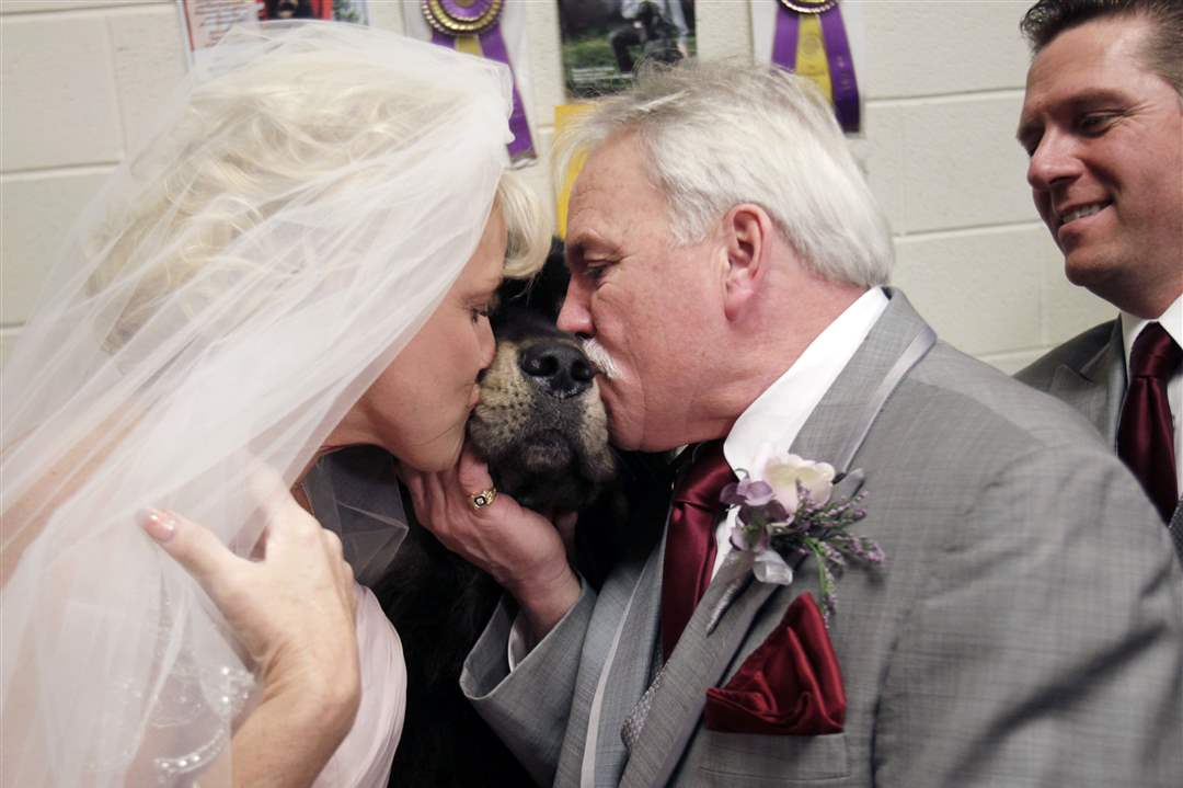 Debbie-Parsons-left-and-Brady-Slayton-kiss-their-dog-a-Tibetan-mastiff-named-Major