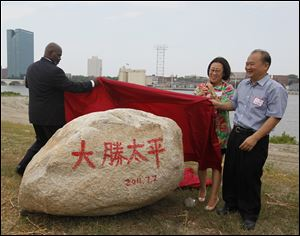 Mayor Mike Bell, Yuan Xiaohong, and Wu Kin Hung unveil a symbolic rock at a July, 2011, event marking the Chinese investors' purchase of 69 acres of Marina District land in East Toledo. The rock, adorned with the Chinese characters for their company, Dashing Pacific, symbolizes steadiness, Mr. Wu said through a translator.