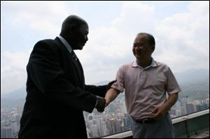 Toledo Mayor Mike Bell, left, shakes hands with developer Wu Kin Hung atop the Empire Building in Shenzhen, China, in May, 2011.