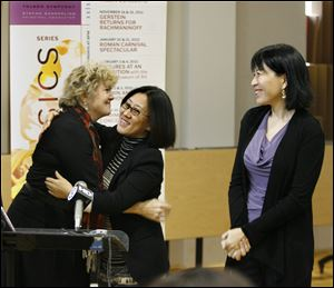 Amy Chang, right, watches as Kathy Carroll, president and CEO of the Toledo Symphony, embraces Yuan Xiaohong of the Dashing Pacific Group,   following an announcement that they would sponsor a trip to China for the Toledo Symphony.