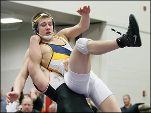 Achbold's Austin Ripke is taken by Seneca East's Nick Hughes during the 160 pound match during the finals of Division III district wrestling Saturday, at Owens Community College in Perrysburg Township, Ohio. Ripke won 6-4.