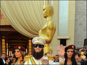 Sacha Baron Cohen, center, and guests arrive before the 84th Academy Awards.