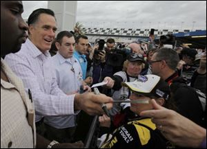 Republican presidential candidate, former Massachusetts Gov. Mitt Romney signs autographs for fans as he visits Daytona International Speedwa