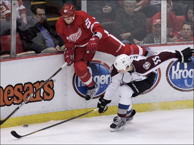 Avalanche top Detroit The Detroit Red Wings' Kyle Quincey (27) goes up against the boards to chase the puck against the Avalanche's Cody McLeod.
