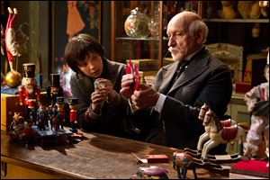 Asa Butterfield, left, portrays Hugo Cabret, and Ben Kingsley plays George Melies in a scene from 'Hugo.'