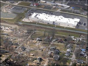 This aerial photo shows a path of damage stretching west from the backside of a Wal-Mart Supercenter to the east in Harrisburg, Ill.