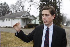 Democratic hopeful Graham Veysey of Cleveland holds a news conference in front of Marcy Kaptur's house in Toledo, one of the targets of the latest super PAC television ad.