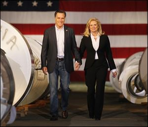 Mitt Romney and wife, Ann, walk between metal coils at Universal Metals LLC in North Toledo on Wednesday.